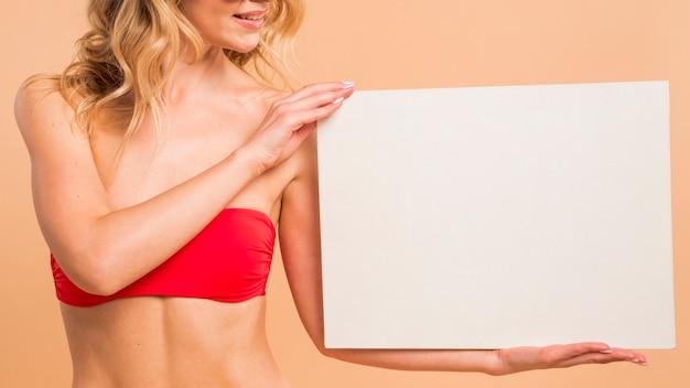 Mujer delgada en tapa roja con papel en blanco