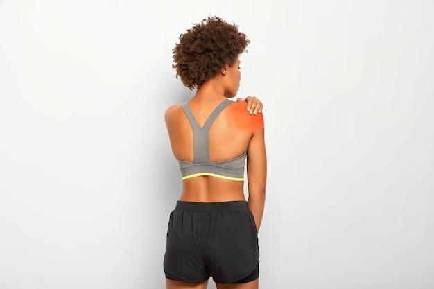 Mujer delgada toca el hombro, retrocede, se lesiona durante el entrenamiento, usa top y pantalones cortos