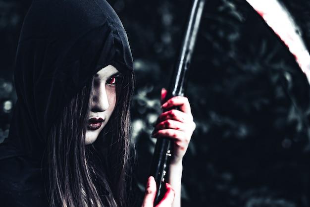 Mujer demonio bruja con sangrienta segadora de pie delante de un bosque misterioso