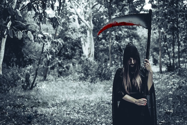 Mujer demonio bruja con segador sangriento de pie delante de fondo de bosque misterioso
