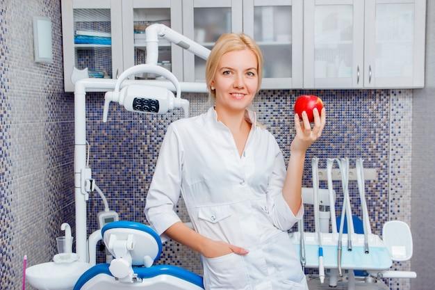 Una mujer dentista en blanco con posturas de manzana contra un equipo dental en un consultorio dental