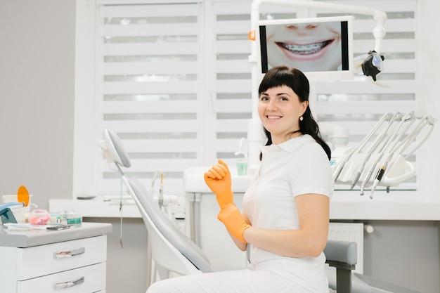Mujer dentista en camisa blanca en el lugar de trabajo