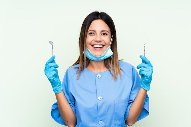 Mujer dentista con herramientas sobre pared verde