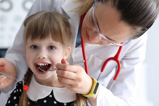 Mujer dentista mira boca abierta litle niña feliz