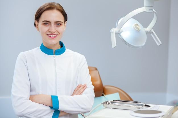 Mujer dentista posando con orgullo en su clínica dental, copia espacio