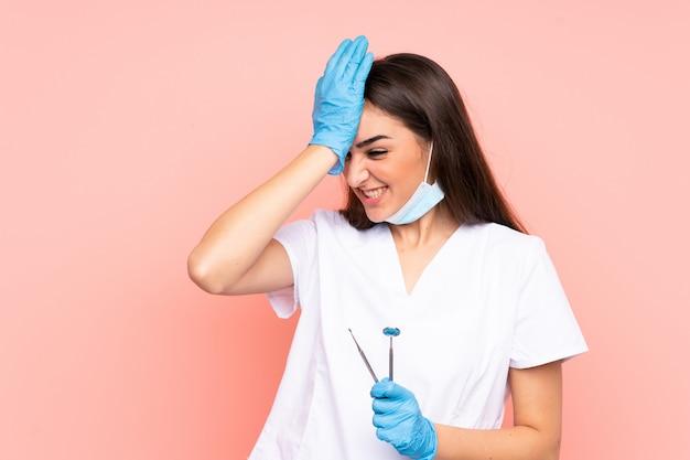 Mujer dentista que sostiene las herramientas aisladas en la pared rosada que tiene dudas con la expresión de la cara confusa