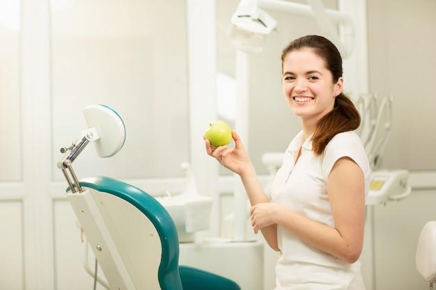 Mujer dentista sonriendo y sosteniendo una manzana verde, cuidado dental y concepto de prevención