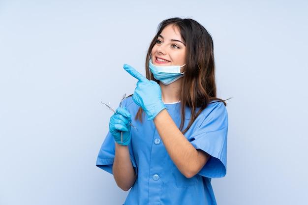 Mujer dentista sosteniendo herramientas sobre pared azul apuntando con el dedo índice