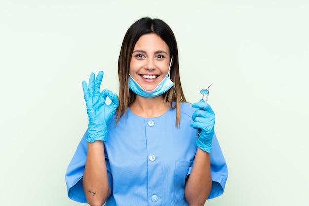 Mujer dentista sosteniendo herramientas sobre pared verde aislado que muestra un signo bien con los dedos