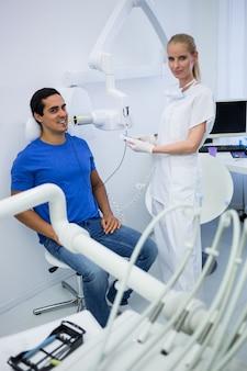 Mujer dentista tomando radiografías de dientes de pacientes