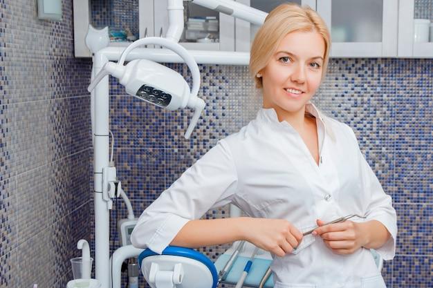 Una mujer dentista en uniforme blanco posa contra un equipo dental en un consultorio dental