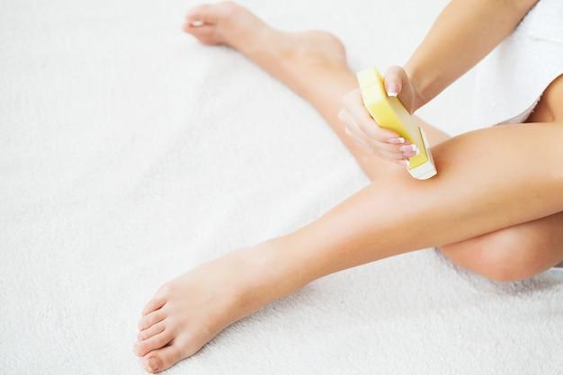 Mujer depilando sus piernas con un depilatorio portátil roll-on