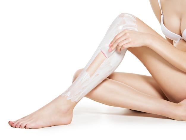 Mujer depilarse las piernas con cera - estudio sobre fondo blanco.
