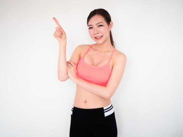 Mujer deporte cruzar el brazo con el dedo acusador hacia arriba y sonríe, concepto de fitness