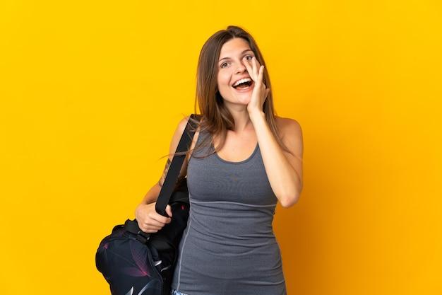 Mujer de deporte eslovaco con bolsa de deporte aislada en la pared amarilla gritando con la boca abierta