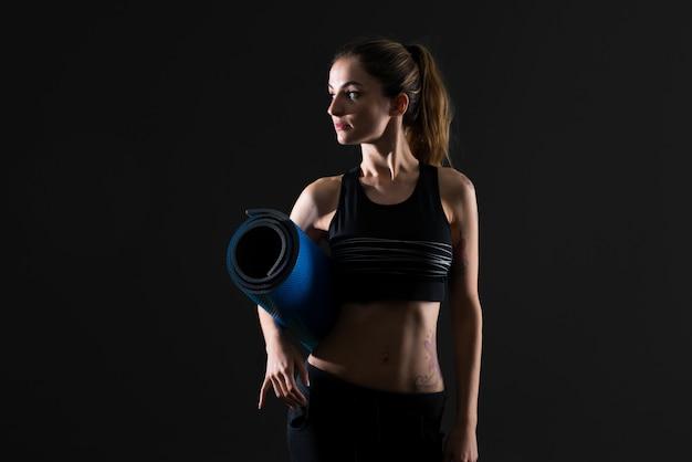 Mujer del deporte con la estera en fondo oscuro