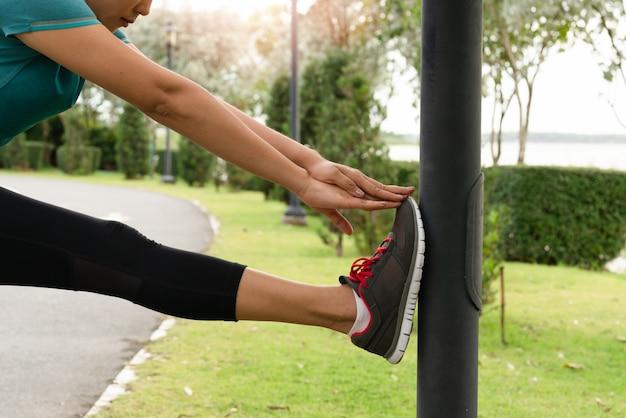 La mujer del deporte está estirando el músculo antes de entrenar