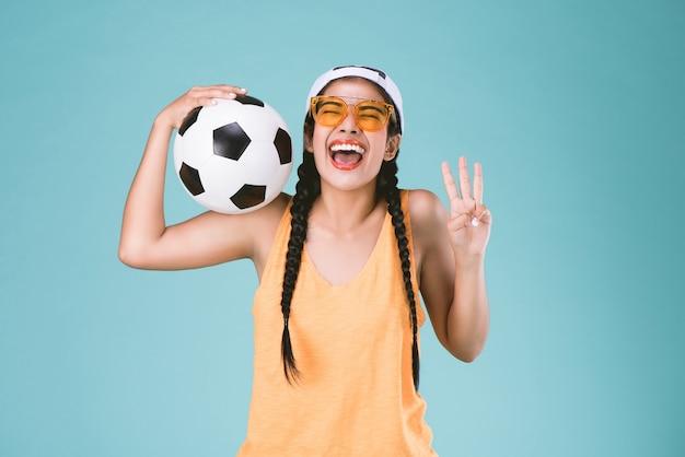 Mujer de deporte fan feliz, sosteniendo un balón de fútbol, celebrando el punto tres dedos hasta el tercer signo