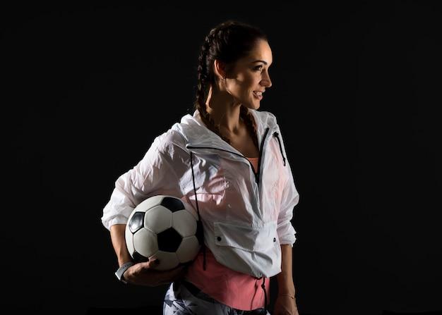 Mujer del deporte en el fondo oscuro que sostiene un balón de fútbol