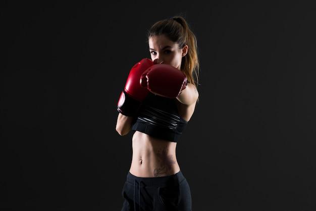 Mujer del deporte con los guantes de boxeo en fondo oscuro
