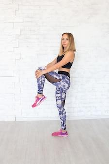 Mujer deporte haciendo ejercicio de piernas para estirar los músculos.
