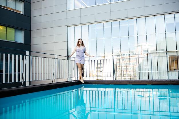 Mujer de deporte de moda bonita joven posando al aire libre en verano en clima caluroso en bikini en la piscina