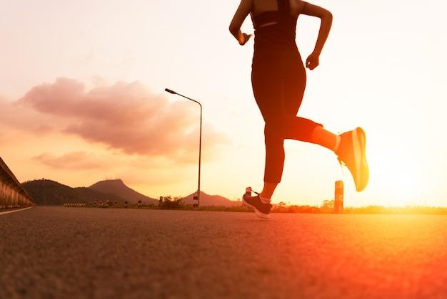 Mujer del deporte que se ejecuta en un camino. entrenamiento de la mujer de la aptitud en la puesta del sol