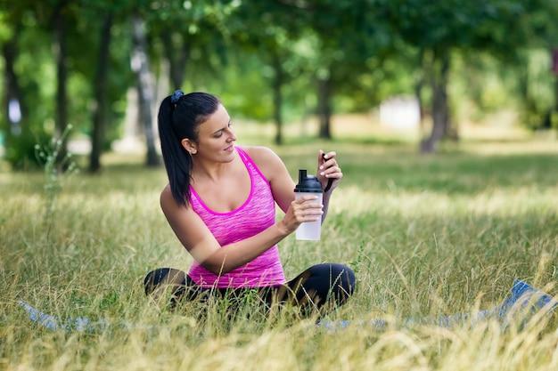 La mujer del deporte sostiene el agua sentada en una alfombra en un parque