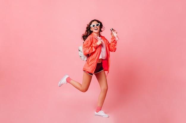 Mujer de deportes en cortavientos, pantalones cortos y zapatillas de deporte se ejecuta en la pared rosa