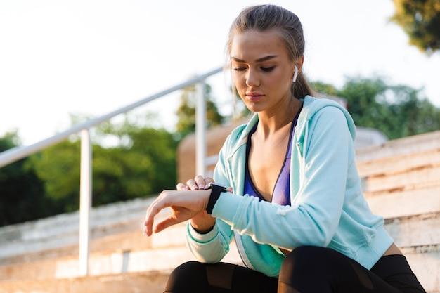 Mujer de deportes en el parque al aire libre escuchando música mirando el reloj.