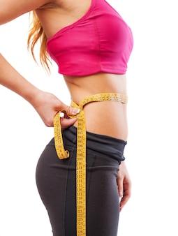 Mujer deportista midiéndose la cintura