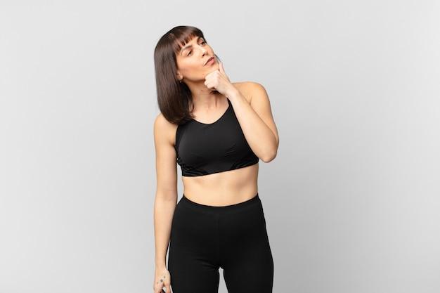 Mujer deportista pensando, sintiéndose dudosa y confundida, con diferentes opciones, preguntándose qué decisión tomar