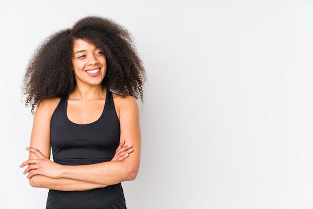 Mujer deportiva afroamericana joven que sonríe confiada con los brazos cruzados.