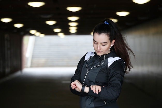 Mujer deportiva al aire libre mirando su reloj de pulsera