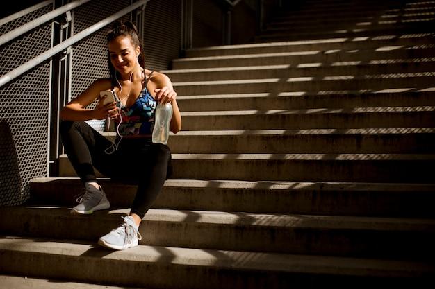 La mujer deportiva apta de los jóvenes que descansa y escucha música en el teléfono móvil después de entrenar al aire libre en las escaleras en el ambiente urbano