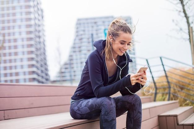 La mujer deportiva apta de los jóvenes que descansa y escucha música en el teléfono móvil después de entrenar