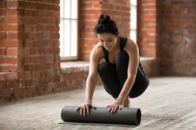 Mujer deportiva apta rodando fitness mat
