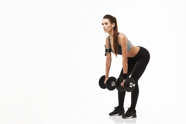 Mujer deportiva de la aptitud joven en los auriculares que entrenan llevando a cabo pesas de gimnasia en blanco.