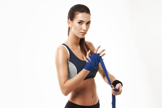Mujer deportiva de la aptitud que enrolla el vendaje elástico a mano en blanco.