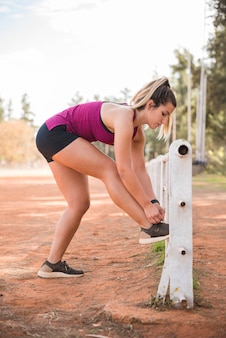 Mujer deportiva atando zapatos en pista de estadio
