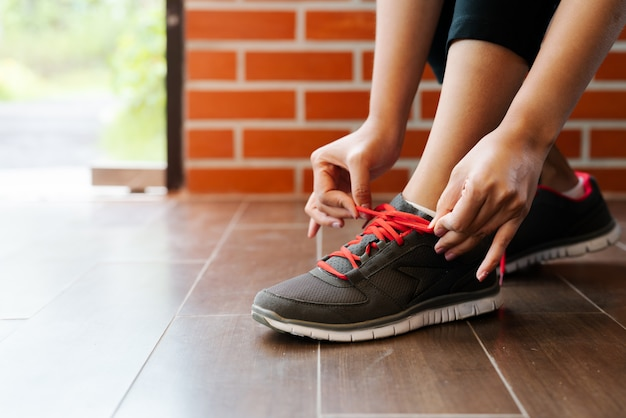 Mujer deportiva atar cordones de los zapatos antes de correr, actividades al aire libre