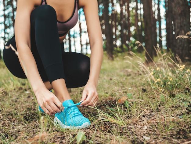 Mujer deportiva atar cordones de los zapatos en los zapatos para correr antes de la práctica en el bosque
