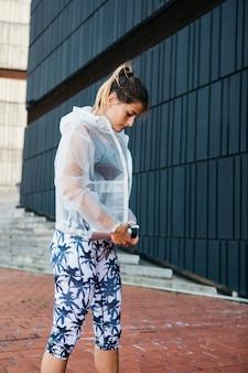 Mujer deportiva con chubasquero en entorno urbano