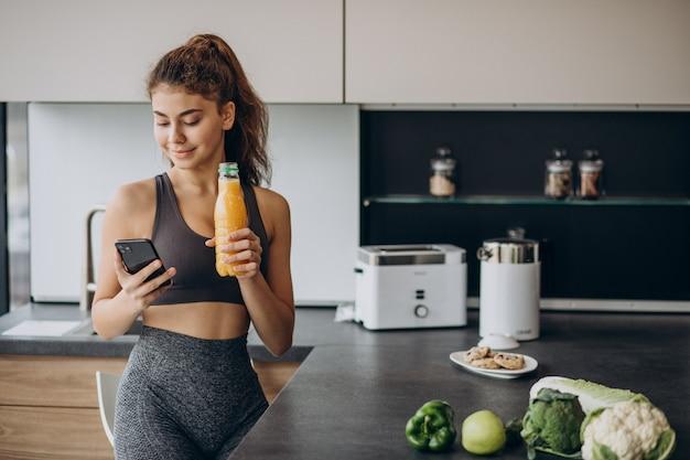 Mujer deportiva en la cocina mediante teléfono móvil