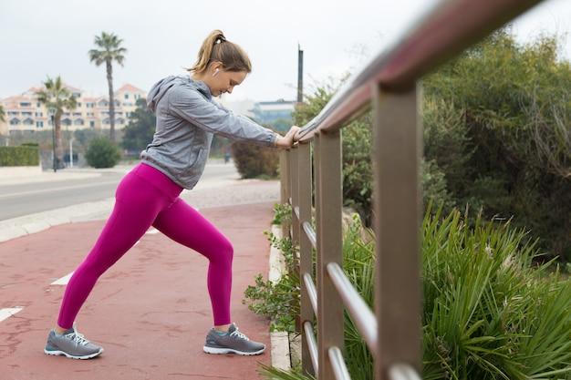 Mujer deportiva concentrada estirando la pierna