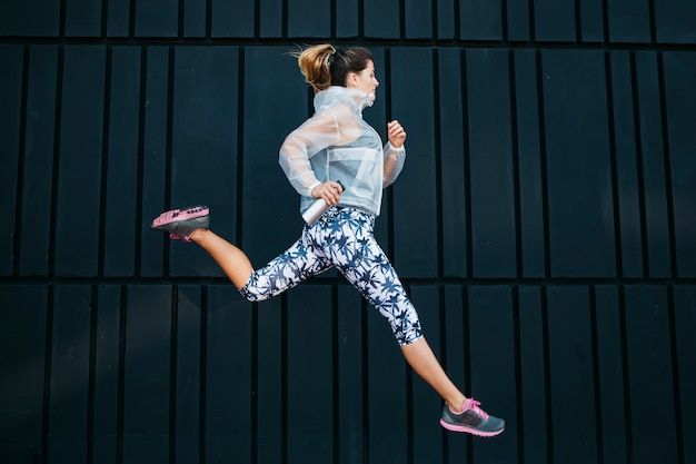Mujer deportiva corriendo en entorno urbano