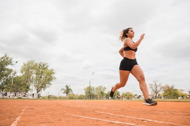 Mujer deportiva corriendo en pista de estadio