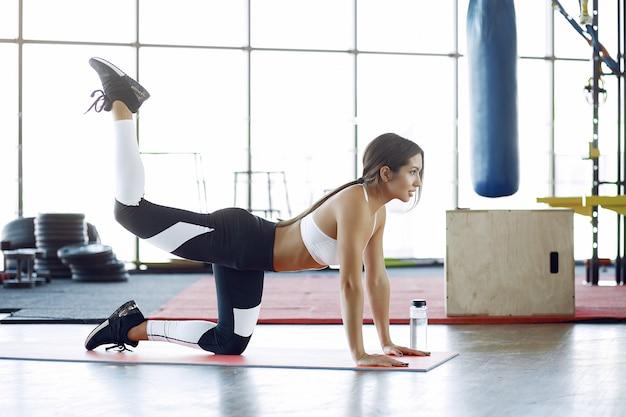 Mujer deportiva entrenando en un gimnasio de la mañana