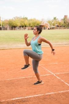 Mujer deportiva entrenando en pista de estadio