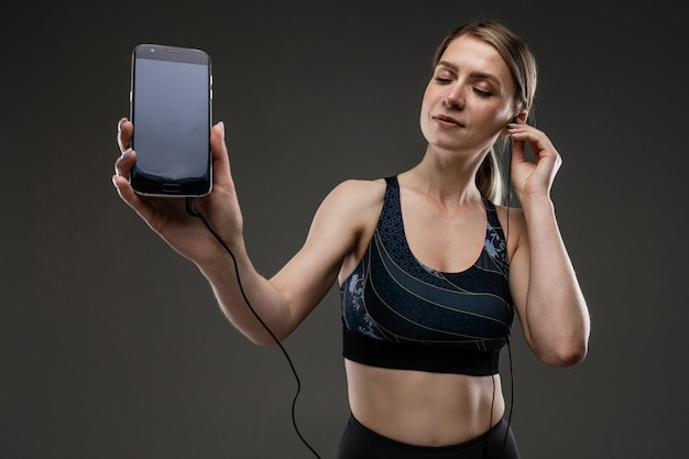 Mujer deportiva escucha música con auriculares grandes
